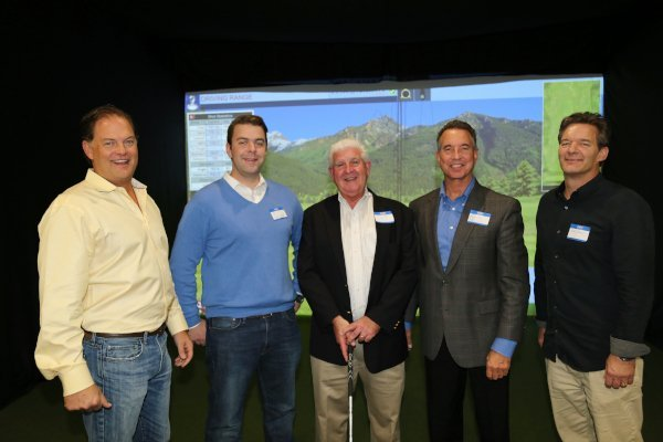 five men wearing business casual clothing standing in front of a simulator screen smiling at the camera