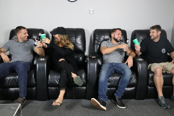 3 men and 1 women sitting in black theater chairs, clinking their drink cups and looking at each other