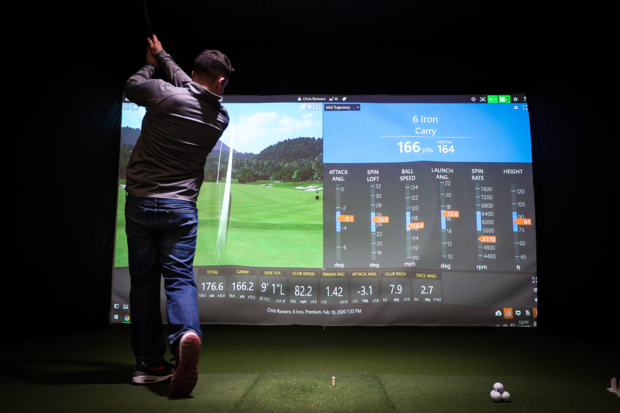 Man wearing gray 1/4 zip and jeans, swinging golf club into simulator screen, TrackMan optimizer and driving range on screen