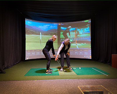 Woman golf instructor, fixing club position for woman student, inside simulator room at GolfCave, wearing athletic apparel