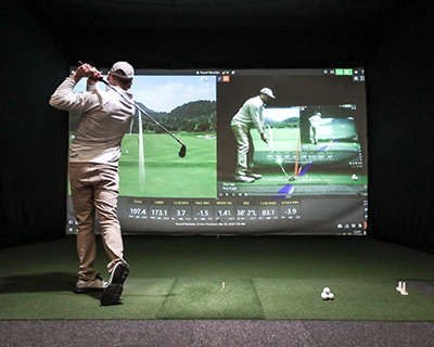 golfer wearing 1/4 zip and khakis swinging into simulator screen, screen showing video of golf swing and driving range