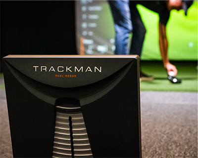 man wearing jeans teeing up in background, TrackMan radar main focus
