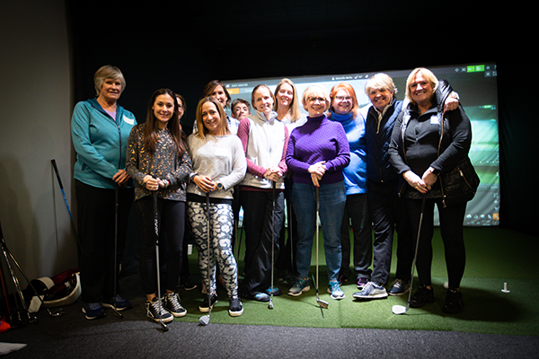 group of women wearing casual clothing, standing on turf, inside simulator room at GolfCave