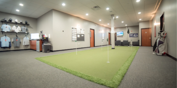 Inside GolfCave lobby, turf putting green, merchandise wall with polos and hats, gray wall and carpet, lounge area in the back