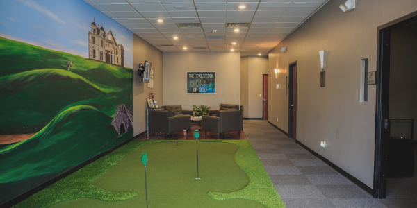 Inside GolfCave lobby, turf putting green, St Andrew's wall mural, gray wall and carpet, lounge area in the back