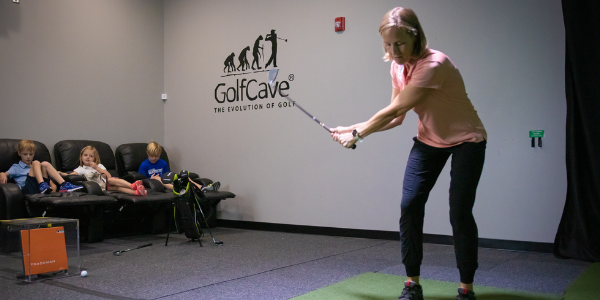 woman wearing pink polo and navy joggers, swing golf club at GolfCave, 3 kids sitting in recliner chair watching in the background, TrackMan golf simulator