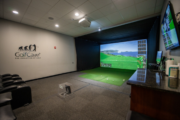 panoramic view of inside a GolfCave, theater chairs, gray walls with GolfCave logo, simulator screen, TrackMan, granite bar and tv